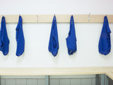 Five Blue Shirts Hanging in Changing Room of Gym