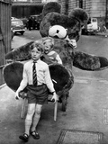 A Boy Gives a Ride to a Little Girl and a 9-Foot Teddy Bear at the Opening of the British Toy Fair