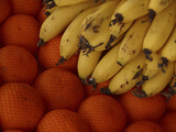 Close-up of a Pile of Fresh Ripe Bananas and Juicy Oranges in a Mesh Net