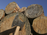 Close-up of an Axe Cutting into a Log Against a Blue Sky