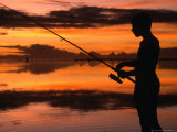 The Silhouette of a Boy Fishing at Sunset in One of the Lagoons Around the Island  Cook Islands