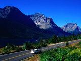 Car Driving on Road with Mountain Range Glacier National Park  Montana  USA