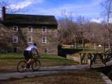 Man Cycling Past Building in Rock Creek Park  Washington Dc  USA