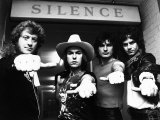 Slade Pop Group 1981 Standing in Front of a 'Silence' Sign with Their Thumbs Out