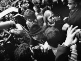 Mick Jagger and Marianne Faithful Make Way Through a Pack of Press Photographers