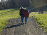 Mother and Daughter Arm in Arm Walking on a Pathway