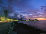 Twilight View of Young Cubans Sitting on City's Seawall