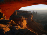 Breathtaking View Down the Canyon from a Warmly-Lit Mesa Arch