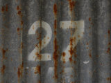Number 27 Stenciled into a Rusty Metal Surface