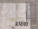Exterior Wall of Building with Wooden Door and Radio Word Stencil
