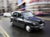 London Cab Traveling Through Traffic on a Rainy Day  England  London