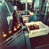 Peroni Factory  Worker Operating a Machine That Moves Bottles Full of Beer