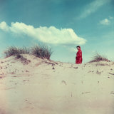 Young Woman Wearing a Red Gown Walking Between Some Sand Dunes