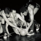 Portrait of Three Basket Players Fighting for Possession of the Ball