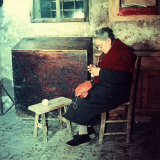 Elderly Woman Sitting and Working on a Shirt in a Rural House