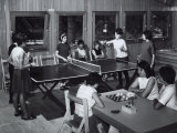 Two Girls Sitting at a Table are Playing Draughts  Four Young Woman are Playing Ping-Pong