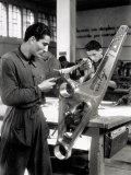 Technician Grinding a Piece of Metal Inside a Caproni Hangar