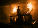 Flames engulf a house during a forest fire