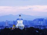 An Illuminated White Pagoda and City Buildings at Sunset  Beihai Park  Beijing  China