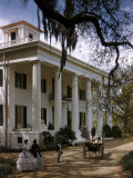People in Period Costumes Stand Outside Greek Revival Plantation Home