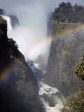 Rainbow Spans Gorge Below Victoria Falls  Mist Rises from Falls