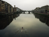 Lone Rower Plys the Calm Waters of a Canal in Florence  Italy