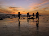 Children Playing on the Beach at Sunset with Family in the Background
