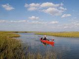 Sea Kayaker and Fisherman Paddles Through a Salt Water Marsh
