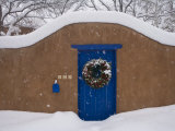 Snow Covered Christmas Wreath Adorns a Blue Door in Santa Fe