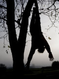 Spooky Fog Outlines a Halloween Dummy Hung from a Tree Branch