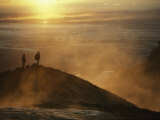 Two Silhouetted Men at Twilight Amid Geothermal Steam on Mountain Top