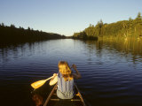Woman Paddles a Canoe on a River in the Adirondacks
