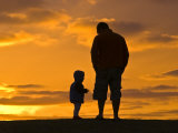 Father and His Baby Son Watch the Sunrise from a Coastal Hilltop