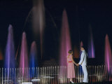 Couple Holding Hands Watches Water Fountains Illuminated at Night