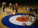 Women Sweep the Ice Ahead of a Curling Stone During a Curling Match