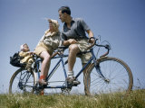 Man and Woman Straddling Tandem Bicycle Look at Child in Back Seat