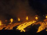 Molten Slag Cascades Down a Hillside at Night