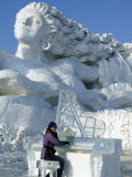 Harbin City  A Tourist Is Playing a Sculpted Ice Piano  Snow and Ice Festival  China