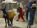 Afghan Woman Walks Along with Donkey Carrying Jerry Cans Filled with Water in Kabul  Afghanistan