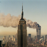 Twin Towers of the World Trade Center Burn Behind the Empire State Buildiing  September 11  2001