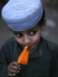 Boy Eats an Ice Lolly in a Neighborhood on the Outskirts of Islamabad, Pakistan Papier Photo