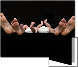 Feet of Caucasian Family  Parents and Twin Babies Against Black Background