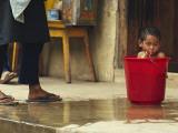 Bhutanese Boy Bathing in a Bucket