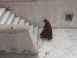 A Tibetan Nun Climbs a Staircase