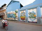 Motorcyclist Passing Night Club with Graffiti Mural