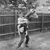 Boy Holding Brother Upside-Down in Backyard