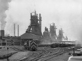 Industrial Site With Trains on Intersecting Tracks  Blast Furnaces in Background