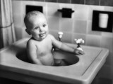 Baby Sitting in Porcelain Sink in Bathroom  Sticking Out Tongue