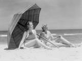 Two Women Sitting on Beach Under Parasol