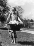 Woman Wearing Apron  Carrying a Wicker Basket of Clean Laundry Outdoors